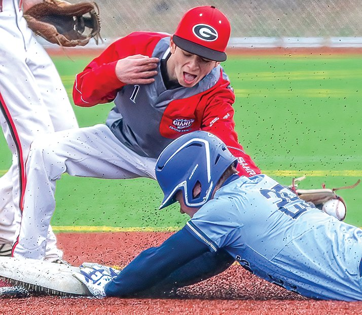 Zach Cheney kicks up synthetic pebbles as he slides for a steal at Mesabi East.