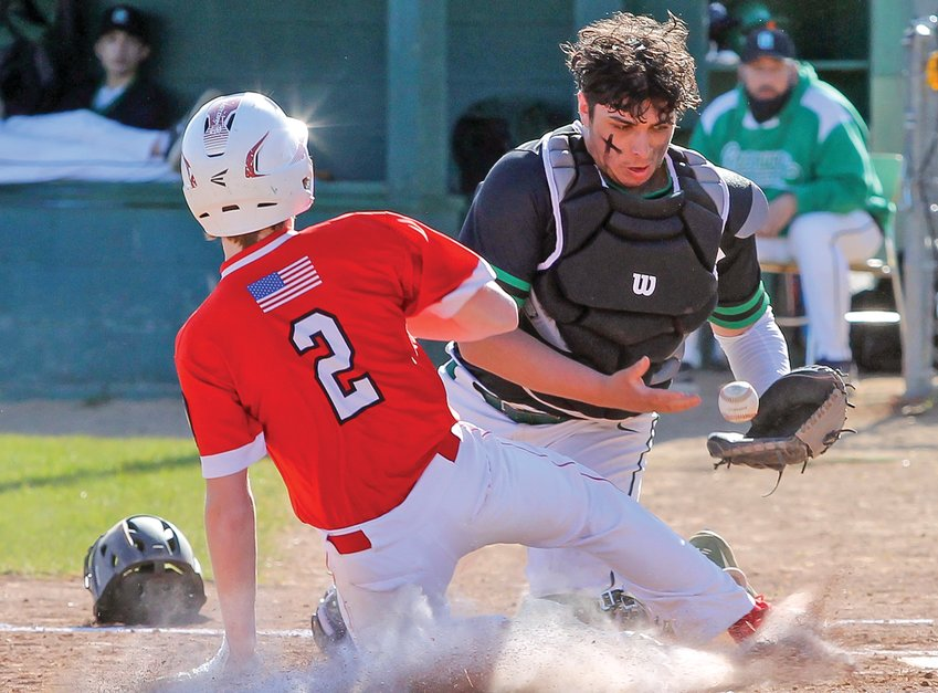 Ely sophomore Logan Loe slides safe into home during last Friday's contest with Greenway.