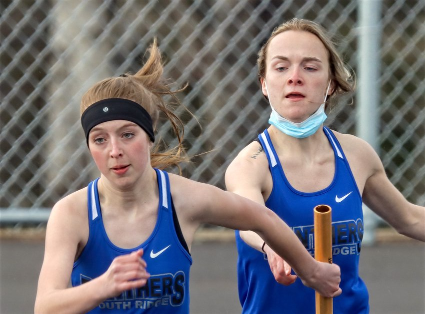 North Woods senior Joey Lakoskey passes the baton to a South Ridge teammate during the 4x100 relay.