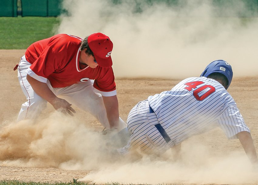 Ely third baseman Lane Anderson puts the tag, too late, on a Carlton baserunner amid a cloud of dust.
