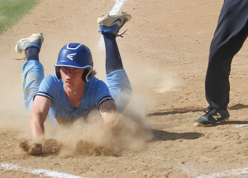 North Woods' Jake Panichi kicks up plenty of dust as he dives safe into home plate.