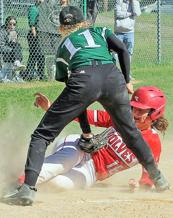 Ely sophomore Rachel Coughlin slides safe into home just ahead of the tag from NER pitcher Thia Lossing.