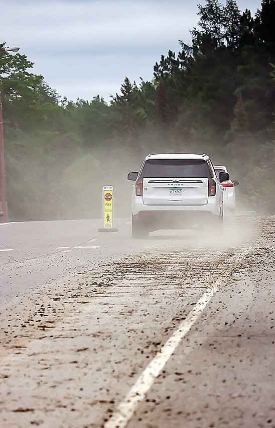Vehicles on Tower's Main Street kicked up dust and created a kind of fog that hung for a time over downtown in the wake of a cement spill that ran the entire length of Tower last Friday. Coming just ahead of the weekend, city clean-up efforts were hampered by heavy weekend traffic.