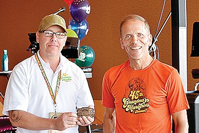 Mike Korpi (right) received a distinctive belt buckle last Saturday after qualifying for the Grandma's Marathon 1,000-Miler Club.