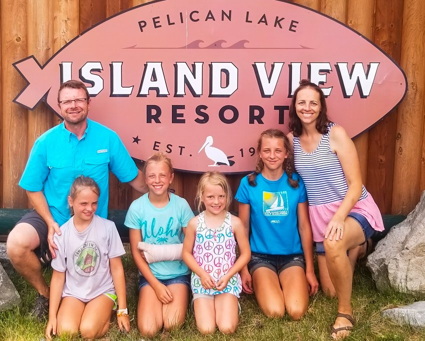 Brett and Alaine Brodeen pose with their daughters Anelise, Corra, Esme and Evelyn in front of their Island View Resort sign at Pelican Lake.