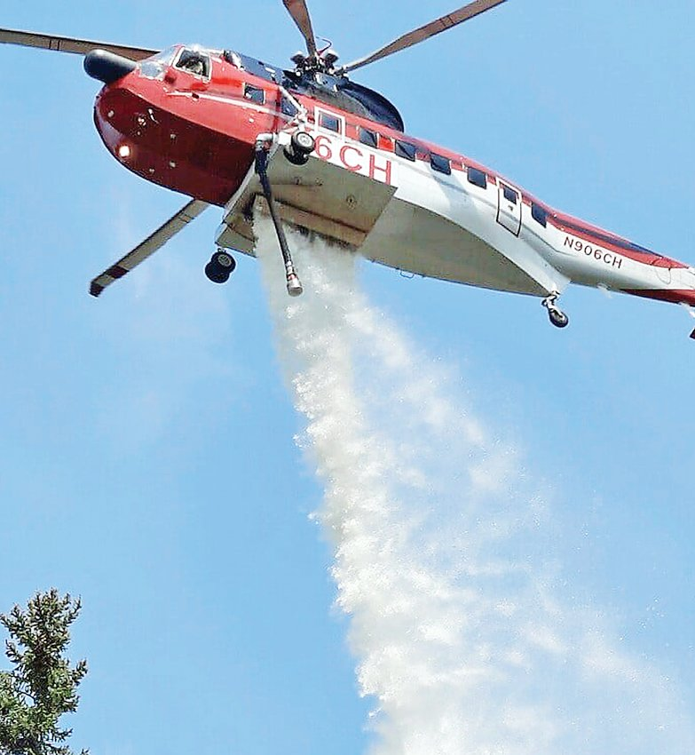 A helicopter dumps a load of water on the Phantom Fire, about 10 miles west of Ely, on Sunday.
