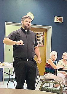 Father Beau Braun greets   parishioners at a recent   potluck in Cook.