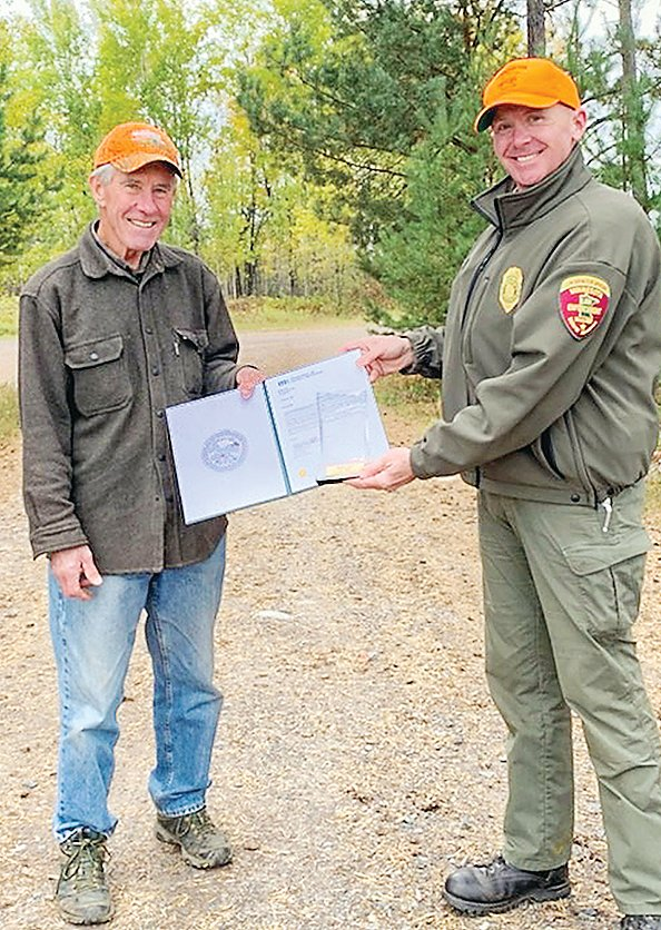 Dick Olson   accepts a certificate   honoring his half   century of volunteer   service as a hunter   education instructor.