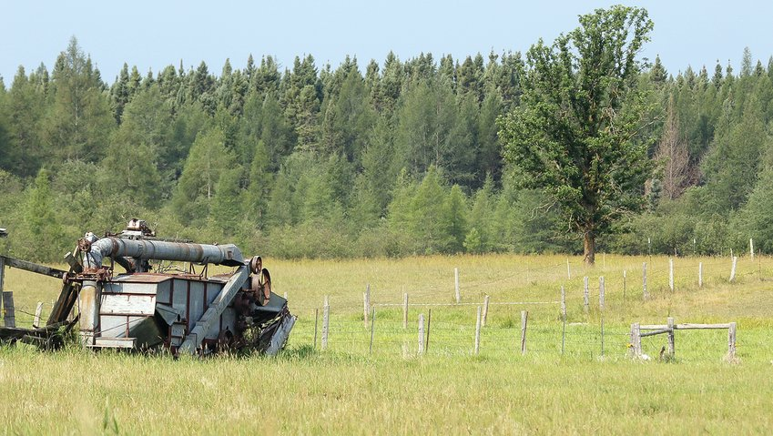 A long-abandoned harvester sits forlornly in a field, backed by tall   tamarack and black spruce in the distance, a perfect   example of the East Little Fork landscape.