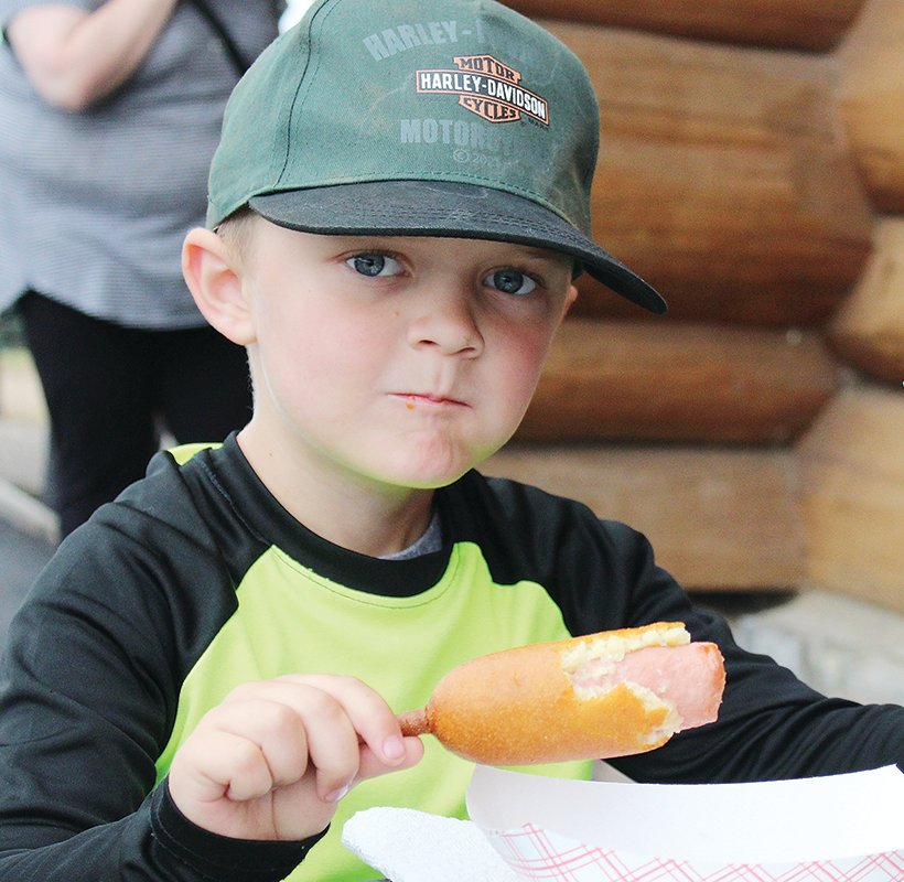 Jayce Walli enjoys a corn dog at the Embarrass Region Fair last weekend.
