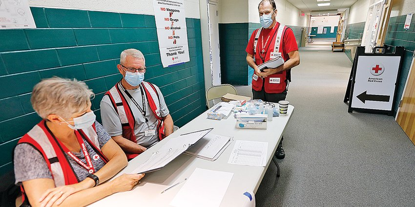 Red Cross shelter manager Rod Winters, standing, and volunteers reviewed the Babbitt shelter supplies inventory Saturday morning at the city's municipal center.