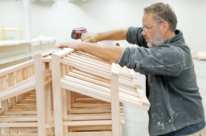 Chris St. Martin builds wine racks for his brother Eric's new Ely Liquor building, opening Friday, Oct. 8.