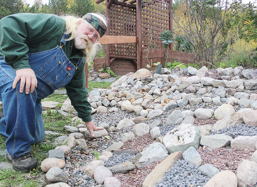 """Gary """"Daddy Willow"""" Culbert has transformed the sloped yard at his home in Soudan into an artistic rock display."""