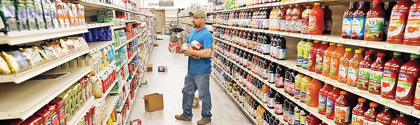 """Robert Norris stocked coffee and tea products this week in preparation for the """"soft"""" opening of the new Zup's Market in the former Shopko building in Ely."""
