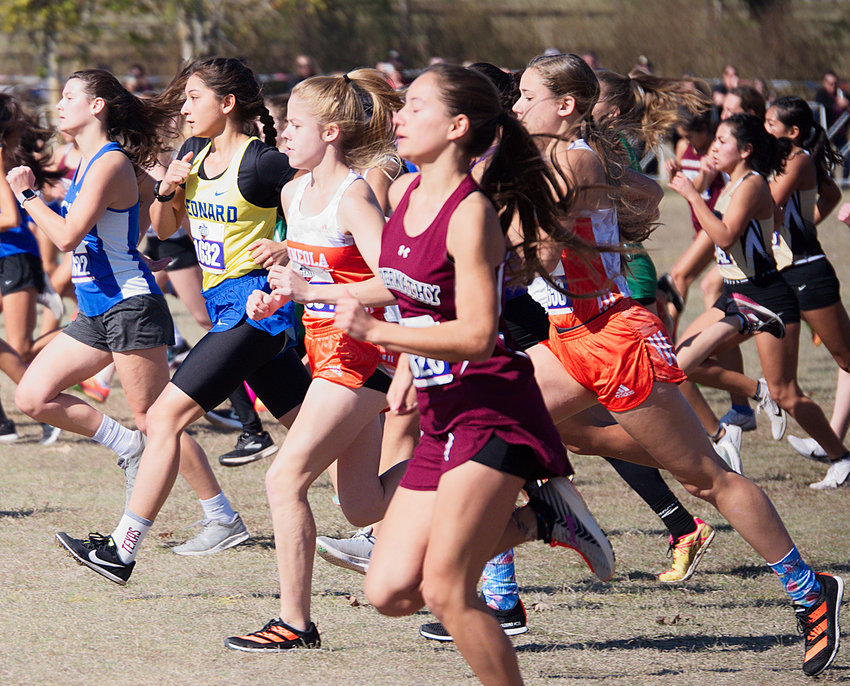 Juliana Stanley and Hannah Zoch, clad in orange, keep up with the rapid pace of their competitors near the front shortly after the start of the 3A girls cross country championship meet at Old Settlers Park in Round Rock on Saturday.