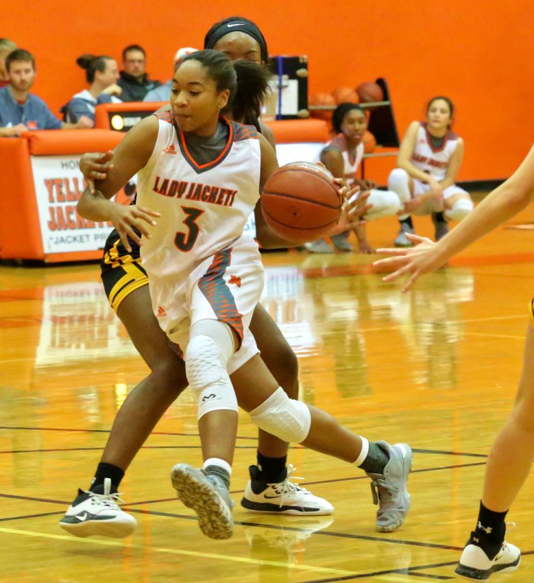 Lady Jacket Sabria Dean drives the lane before dealing an assist to teammate Kelsey Brewington.