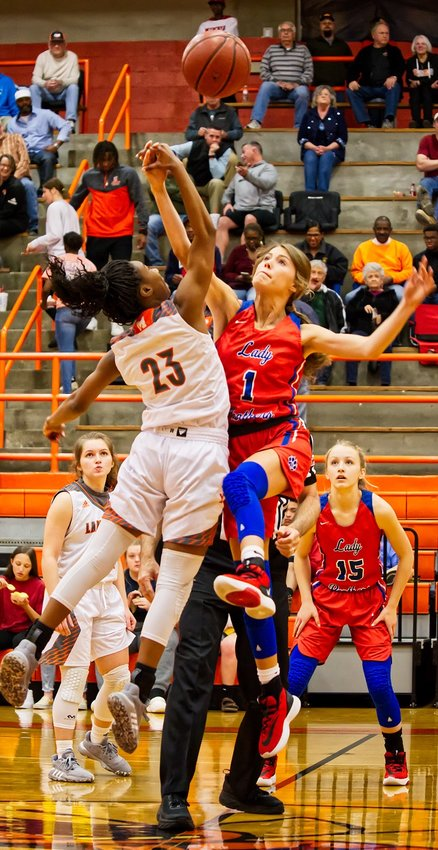 Tahjae Black, 23, of Mineola and Crimson Bryant, 1, tip off as the two neighbors squared off in a district basketball game.