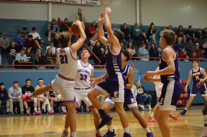 Ben Burroughs (21) comes down hard with a rebound as teammate Jace Reid (33) closes in to help out.