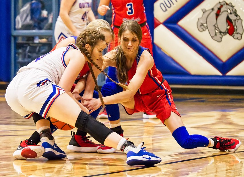Lindsey Hornaday, left, battles Crimson Bryant and Bella Crawford for a loose ball, resulting in one of dozens of jump ball calls during the Wood County square-off last Tuesday in Quitman's Ballard Gym.