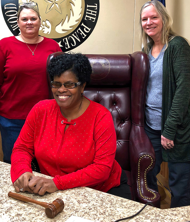Justice of the Peace Janae Holland, seated, with staff members Monica Bailey and Anita Piper.