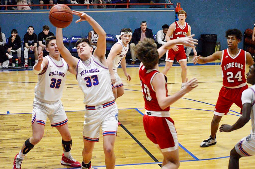 Bulldog Jace Reid (33) fights for a rebound and teammate Chris Chabaud (32)  backs him up as River Chaney (5) breaks out to start a fast break in Quitman's win over Lone Oak.