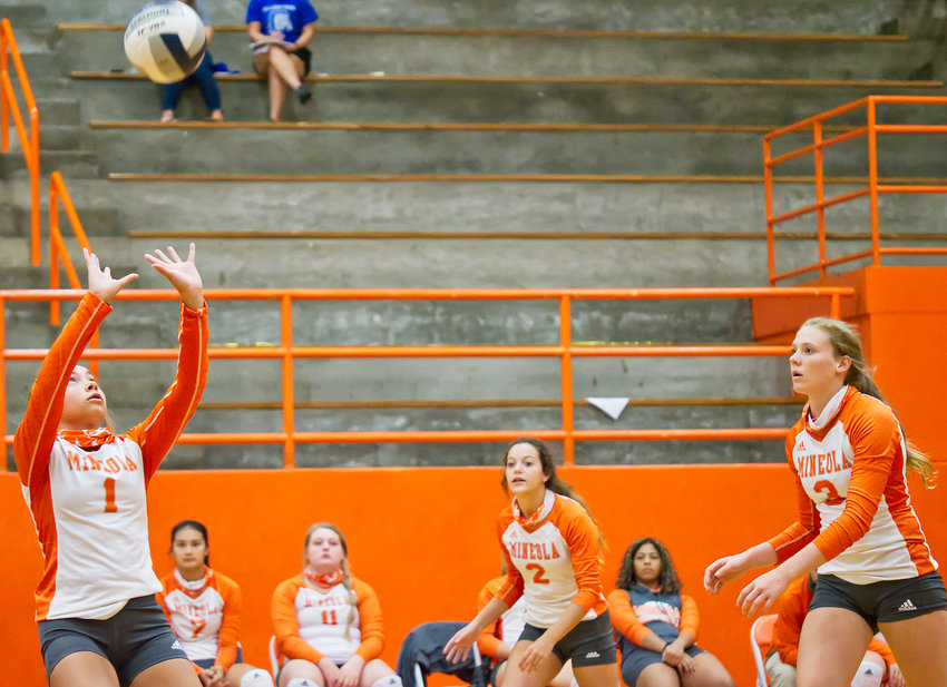 Madison Bloodworth (1) sets the ball for Mineola as Kozbie Riley (2) and Mylee Fischer prepare for the attack.