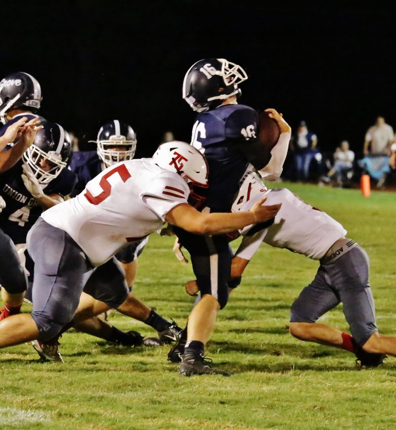 Alba-Golden's Jayden Green (left) and Caleb Anderson crunch a Union Grove ball carrier. (Monitor photo by John Arbter)
