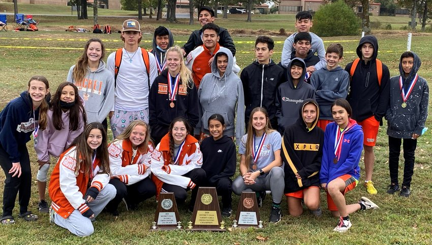 The Mineola girls varsity, boys varsity and girls junior high cross country teams pose with their trophies after placing first, third and second respectively at the district meet last Saturday. (Photo courtesy of TaShara Everett)