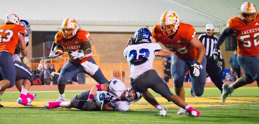 Dawson Elmore (53), Jackson Anderson (56) and Nate Griffen (52) create a wide path for ballcarrier Trevion Sneed to burst through.