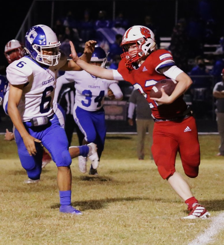 Panther Glen Hartley uses a stiff-arm to gain the edge in action against Celeste. (Monitor photo by John Arbter)