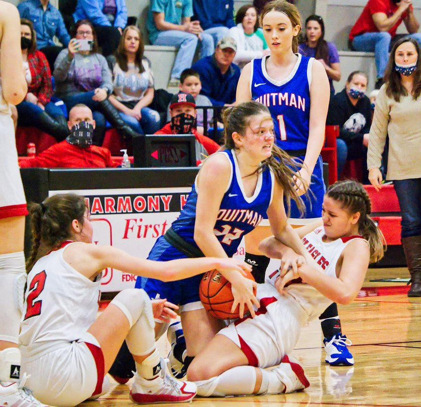 Quitman's Maddy Pence (22) wrestles for the loose ball with Harmony players Monday. The Lady Bulldogs took a 32-31 win.