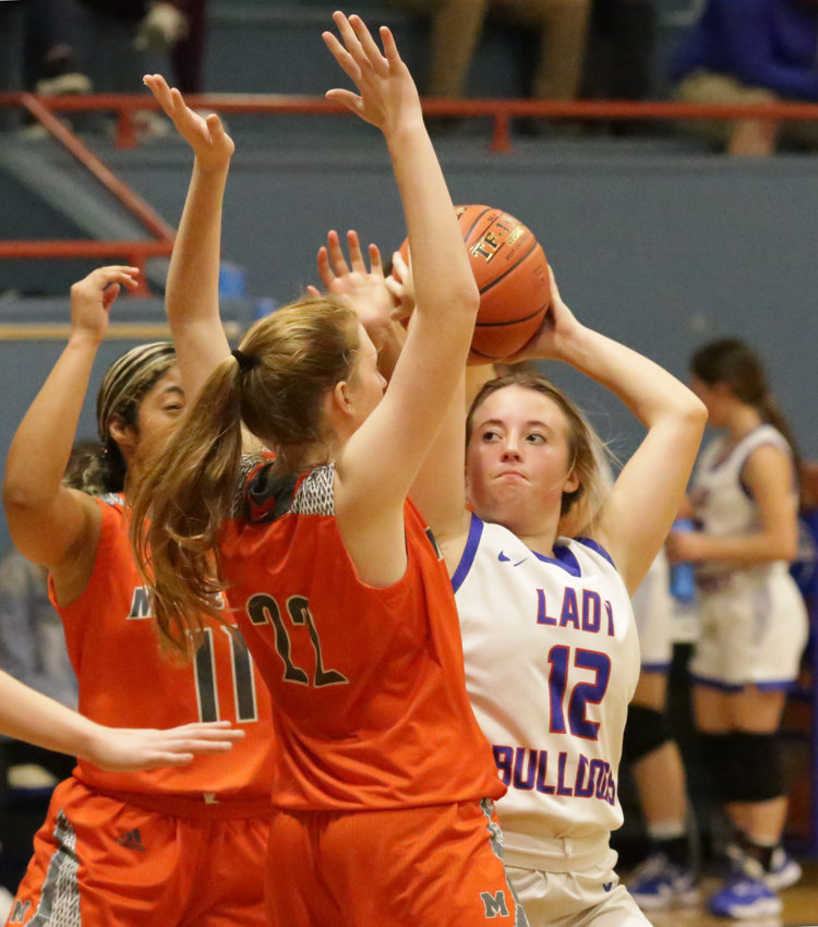 Quitman's Kynlee Love at the high post being defended by Mineola's Jayden Gardner (11) and Macy Fischer (22).