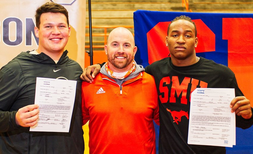 Jackson Anderson, left, and Trevion Sneed, right, flank head football coach and athletic director Luke Blackwell with their signed letters of intent in hand.