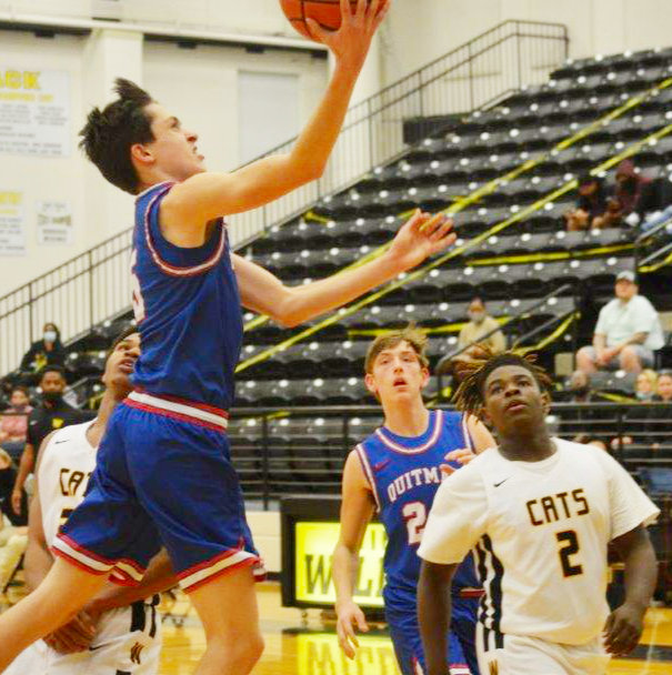 Quitman's Levi Thompson (5) goes to the bucket for a score in the Bulldogs' district win at Winona. Thompson had 19 points and hit on 13-16 free throws.