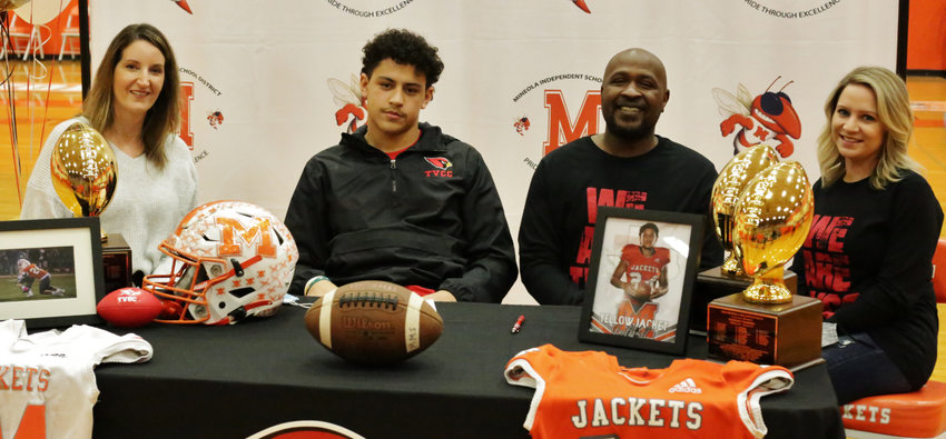 Flanked by his mother Andrea McCoy (left) and his father and stepmother Mark and Micah Kendrick, Yellowjacket senior Kobe Kendrick signs his acceptance of a scholarship to play football at Trinity Valley Community College.