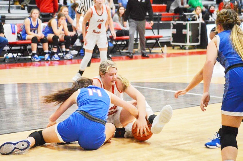Quitman's Ava Burroughs (14) and Winnsboro's Faith Acker (55) fight over a ball in Friday's game at the Lady Raiders new gym. Burroughs would have to leave the game later with an injury after a collision with Acker early in the second half.