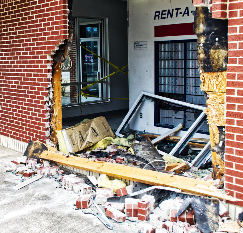 The exterior of the east side of the Post Office building in Mineola, with a hole just wider than the vehicle that smashed through the brick wall.