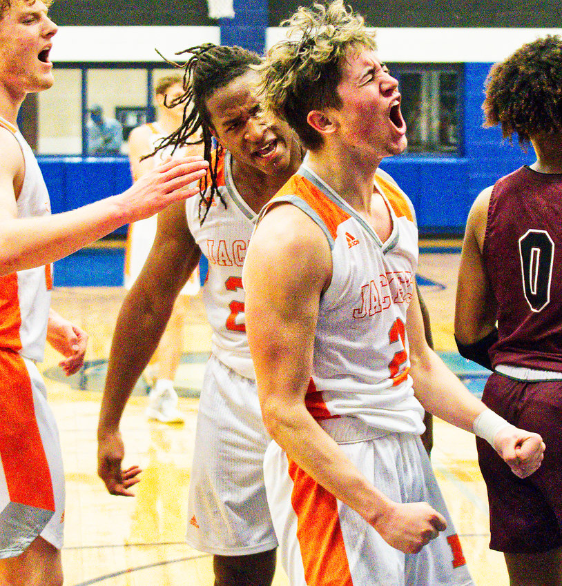 From left, Dawson Pendergrass, Trevion Sneed and T.J. Moreland react enthusiastically to Moreland scoring two points put Mineola ahead by 12 in the fourth quarter while drawing a foul on Jefferson.