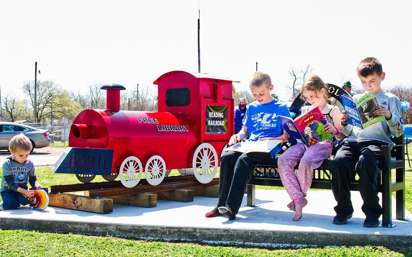 Children enjoy books at the new little free library, dubbed the Reading Railroad, at Iron Horse Square in Mineola. The library was dedicated Saturday.