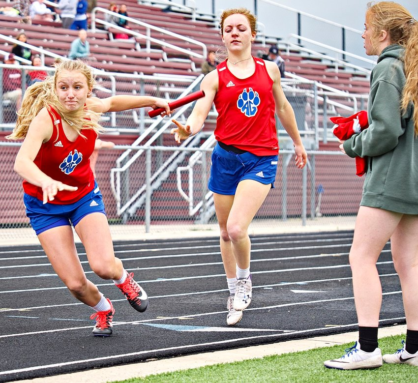 Bella Crawford takes the baton from Cacie Lennon for the third leg of the 4x400 meter relay as Gracie Teel prepares to anchor the race.