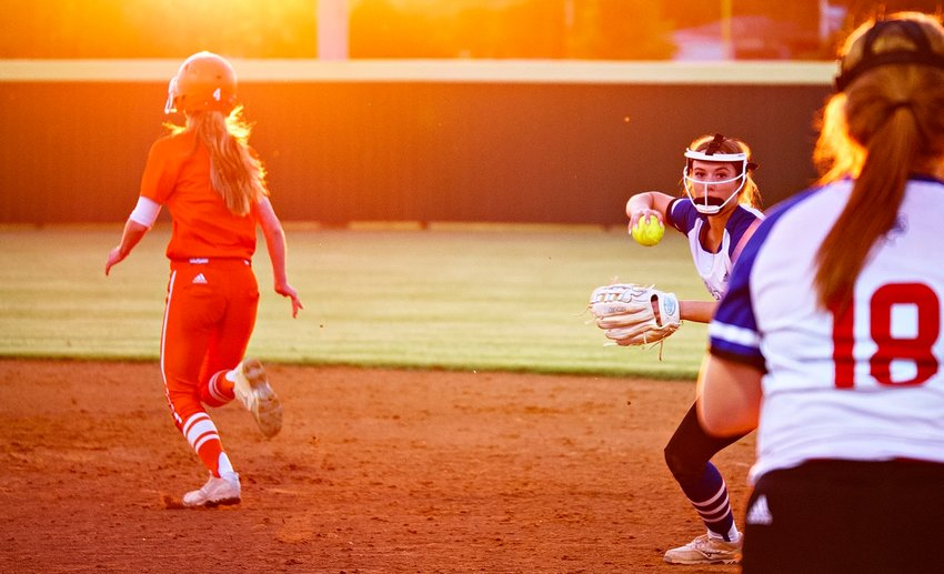 Lindsey Hornaday makes a play to Reiny Luman at first base as Emily Wiley makes her way to second, into the setting sun.