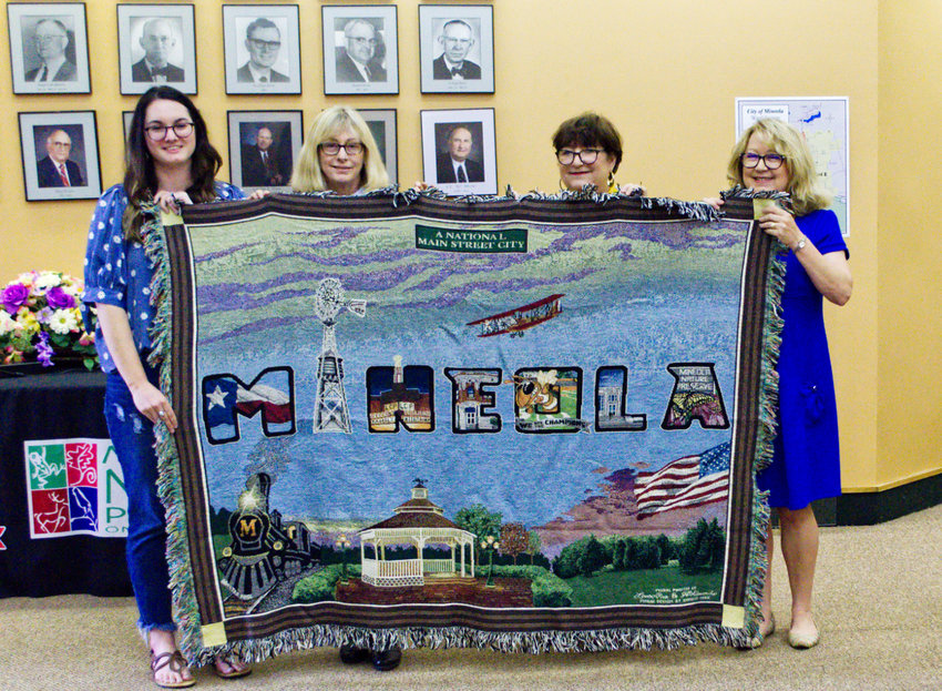 Mural artist Lauren Pitre shows off the new Mineola mural throw rug with museum board members Sharon Chamblee and Wanda Dubbs and Main Street Manager Doris Newman.