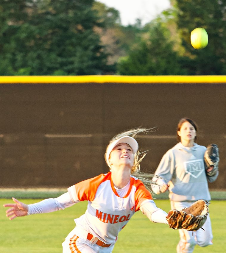 Emily Wiley of Mineola chases a fly ball but the gusty winds pushed it away from her.