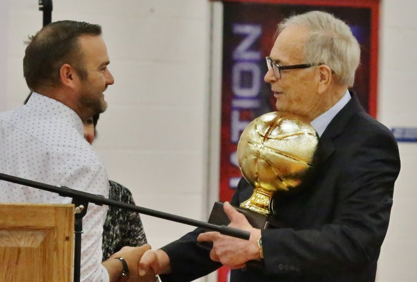 Alba-Golden Athletic Director Drew Webster presents guest speaker and sporting legend Carroll Dawson with a keepsake for his participation at the 2020-21 sports assembly last Wednesday.