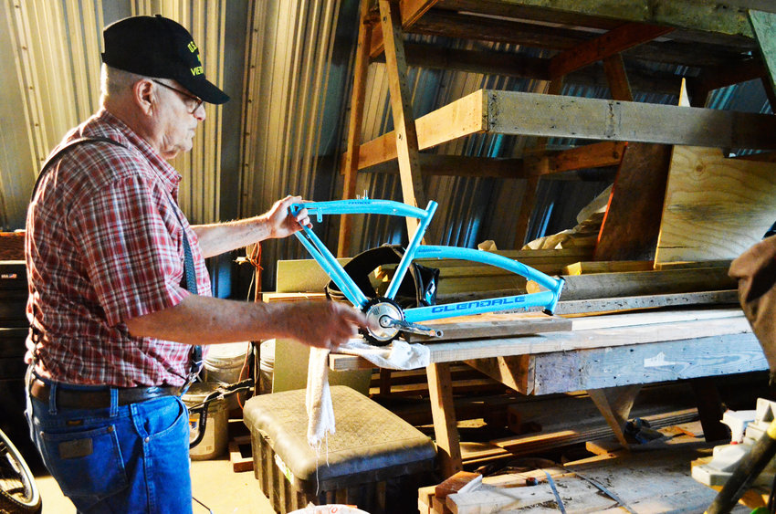 Robert Pierce holds a bike part that he is using to repair other bicycles. The Mineola resident rebuilds older or damaged bikes for those in need.