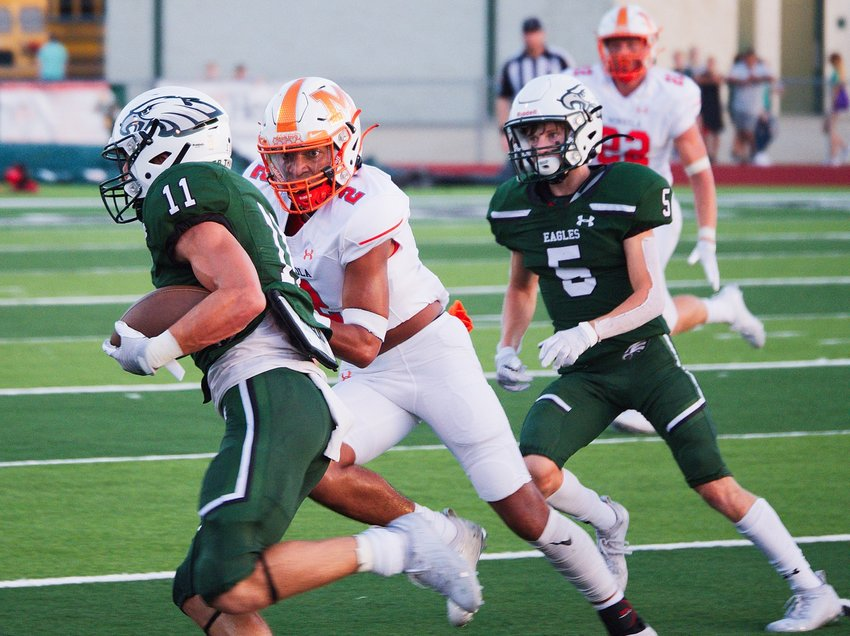 Mineola's Jaxon Holland (2) pursues the Canton runner in Friday's season opener, won 24-21 by the host Eagles. [more photos from Canton]