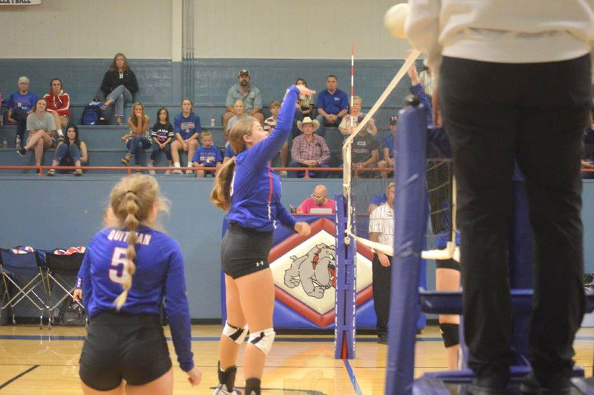 Quitman's Kaysi Parker goes up high at the net to make a play for the Lady Bulldogs.