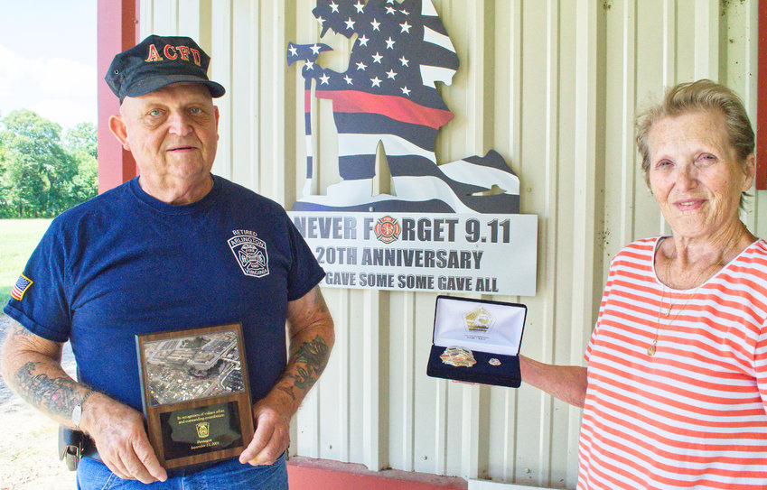 Nelson and Diane Eaton of Lake Fork with his commemorative plaque, badge and pin for his service with the Arlington County, Virginia fire service following the Sept. 11, 2001 terrorist attack on the Pentagon. He recently installed the 20th anniversary memorial at their home.