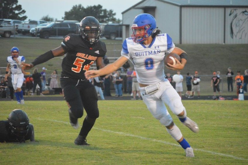 Quitman's Mason Reynolds (8) gains yardage in the Bulldogs' 25-20 win at Queen City. Reynolds scored a pair of touchdowns and had over 100 yards rushing.