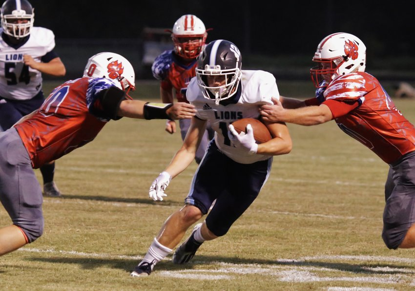 Panther linebackers Ethan Salinas and Shawn Gaskill converge on a Lion runner.